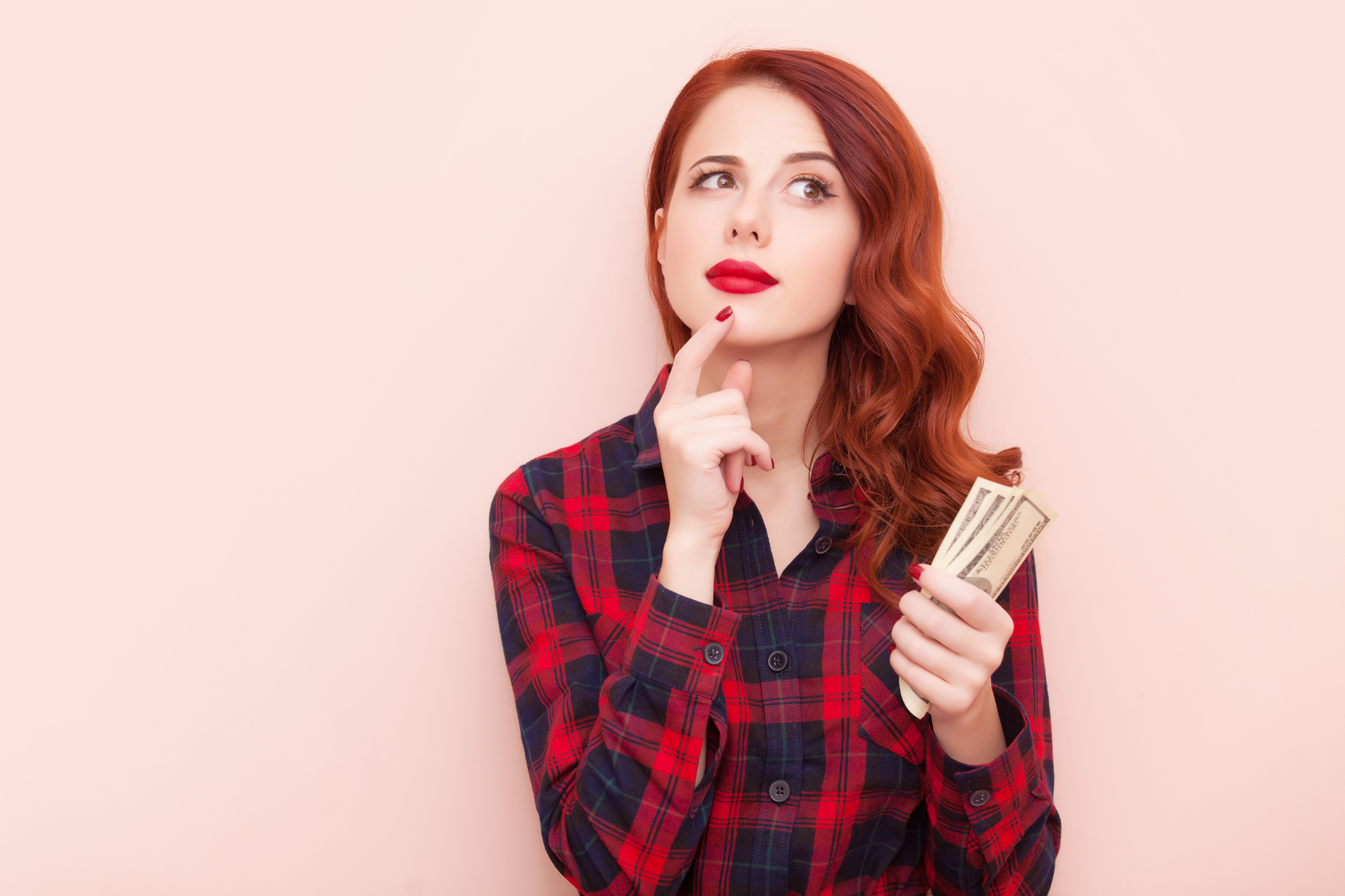 low carb on a budget girl with red hair thinking and holding money